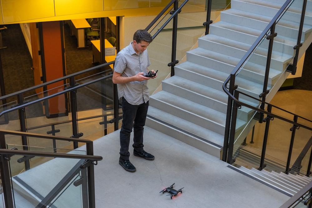 man controlling black quadcopter drone