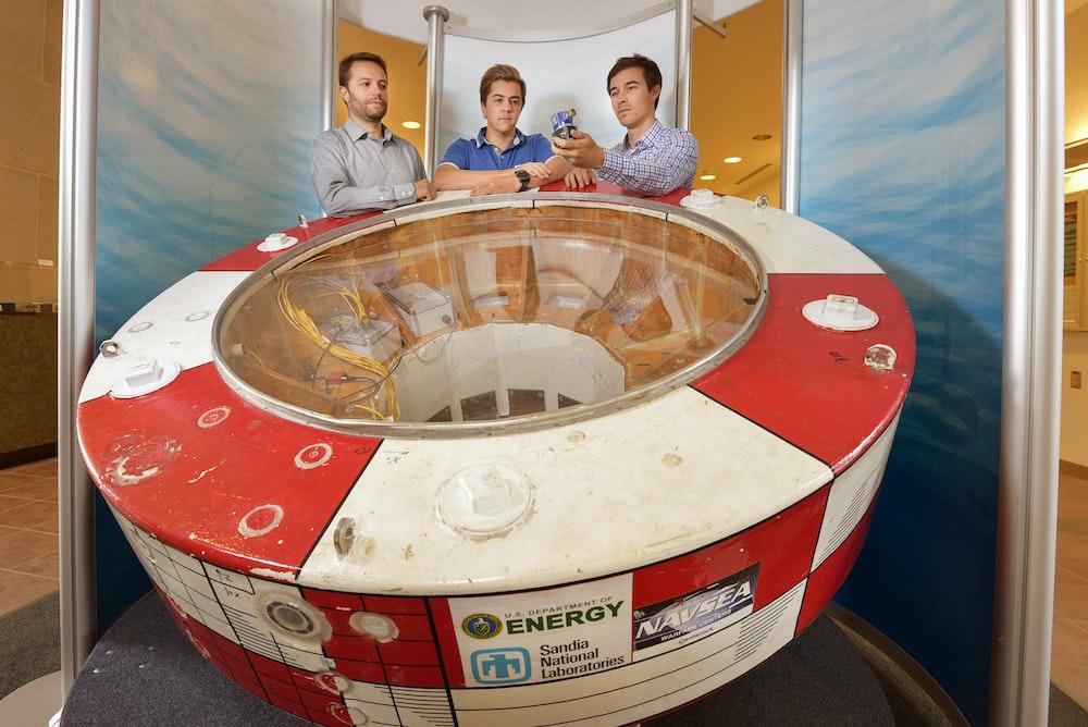 three men standing beside machine