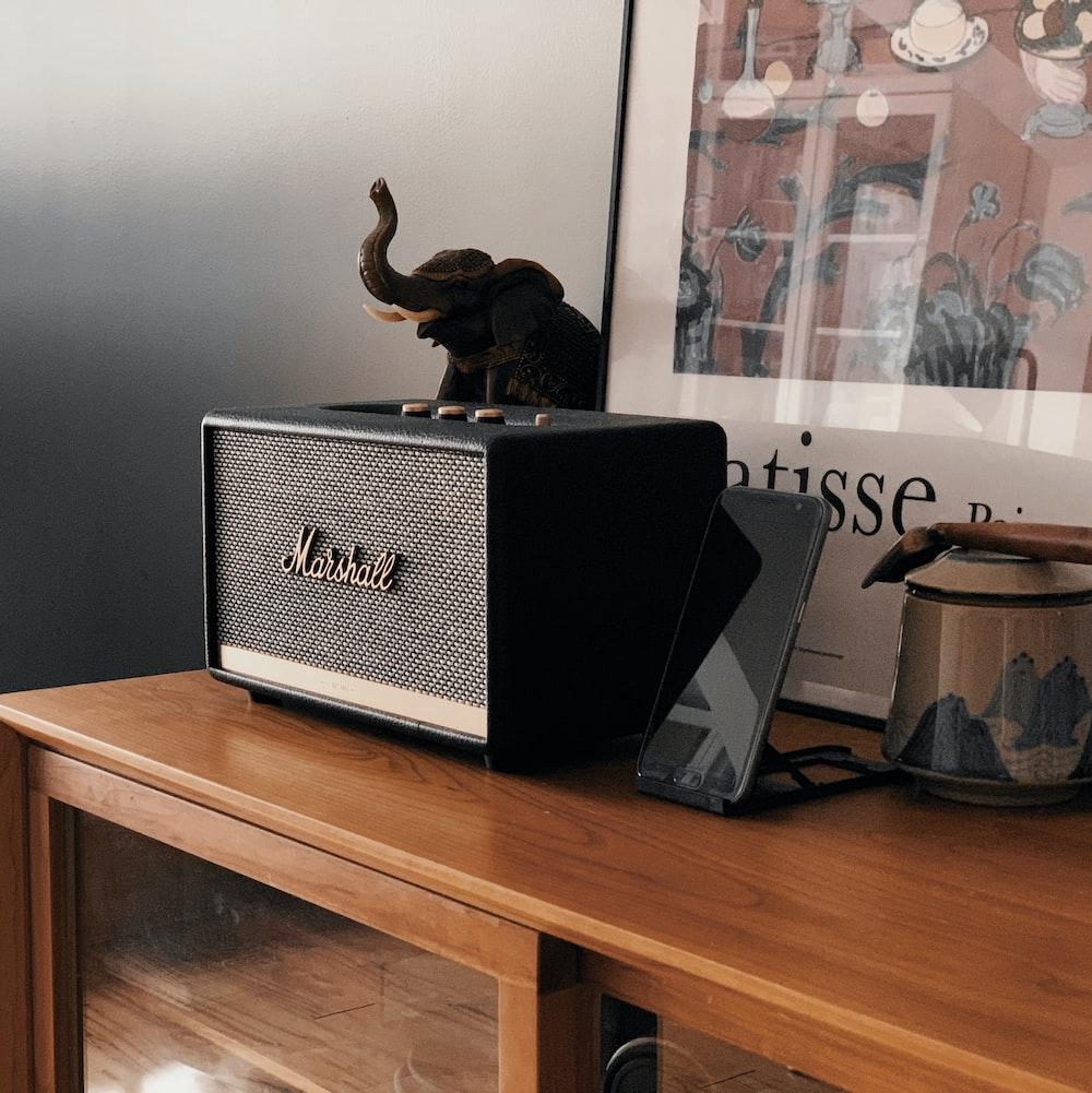 gray Marshall speaker on wooden surface