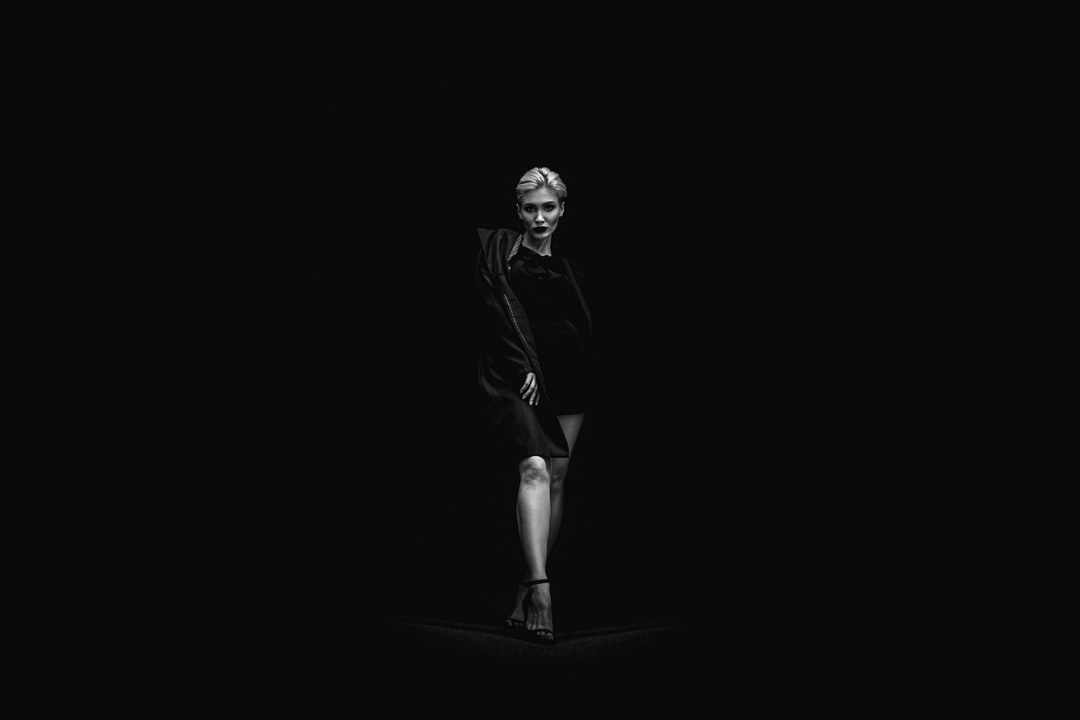 Grayscale Photo of Standing Woman Near Black Surface - unsplash
