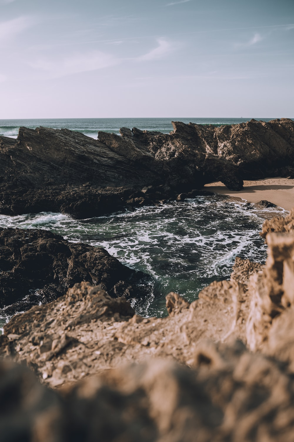 photography of rock formation beside seashore during daytime