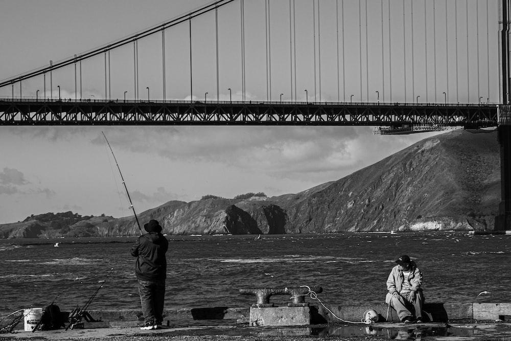 man fishing near bridge