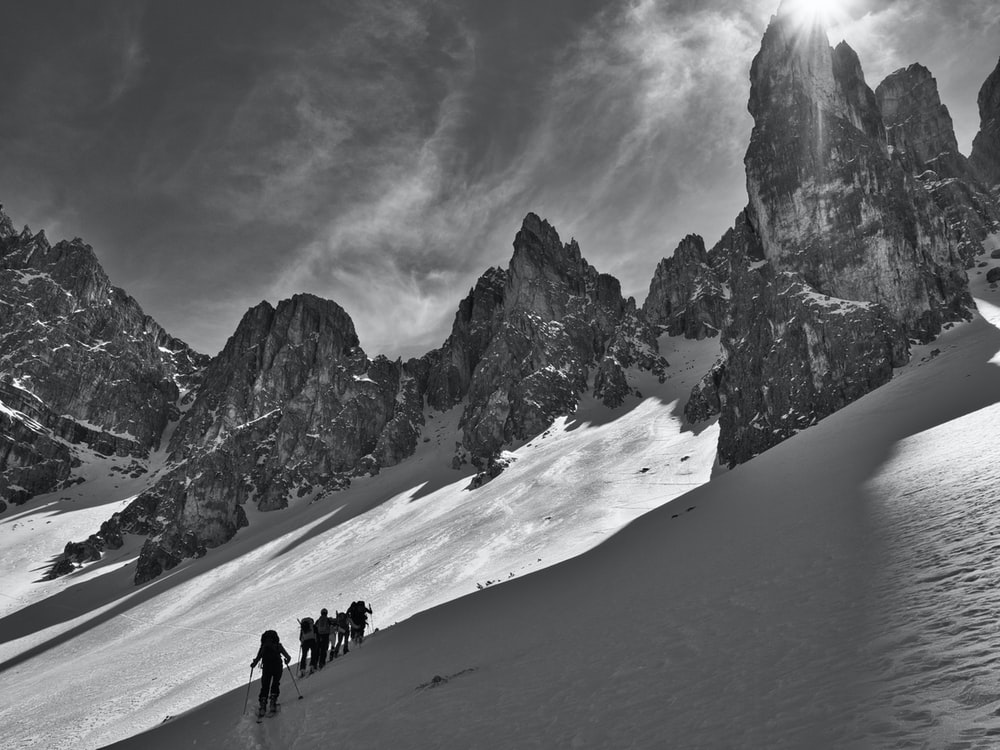 grayscale photography of people walking on snow during daytime