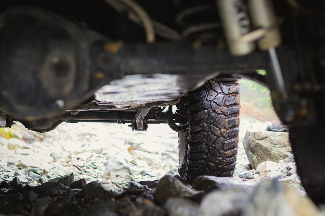 view from underside of 4X4 jeep showing wet knobby tires on rocks