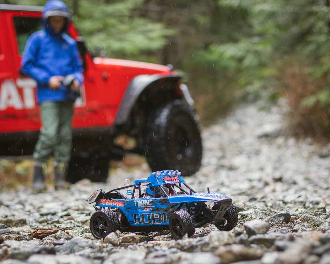 boy in blue rain jacket standing beside red jeep playing with a blue RC car on the rocks
