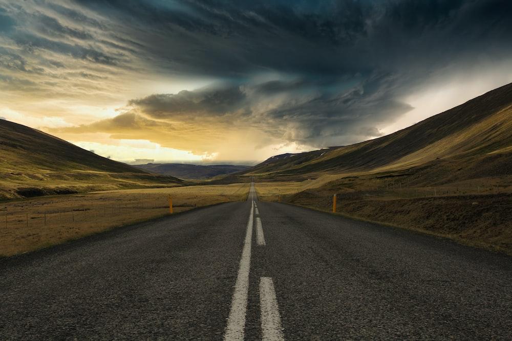 road between brown mountain under cloudy sky