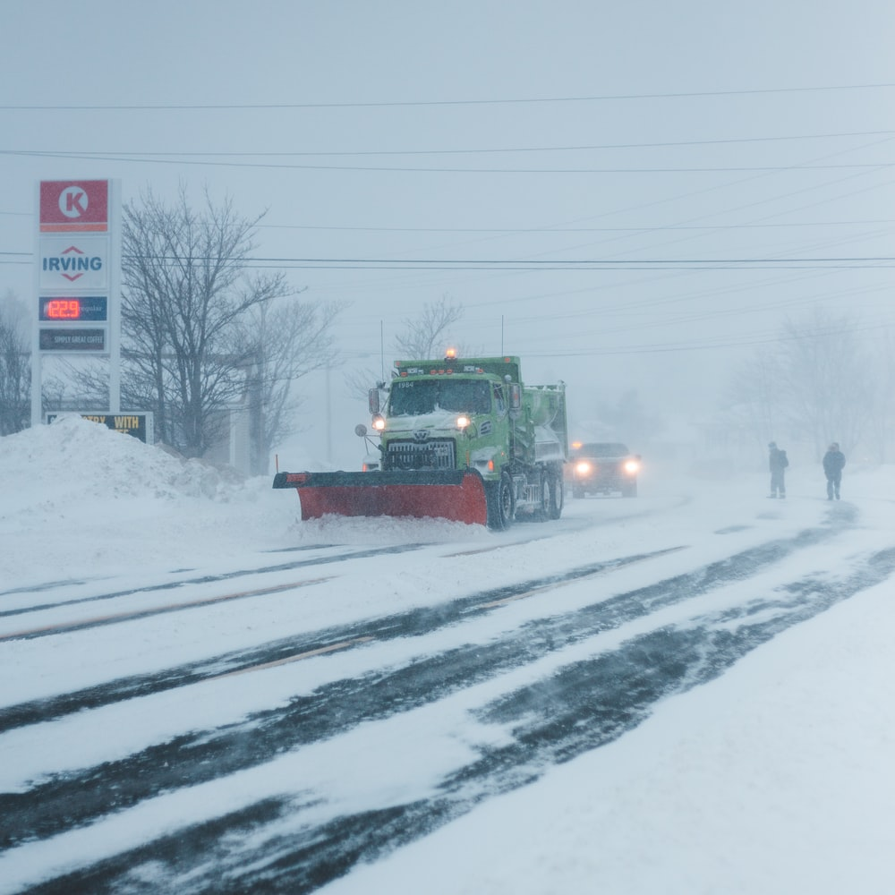 truck plowing snow on road