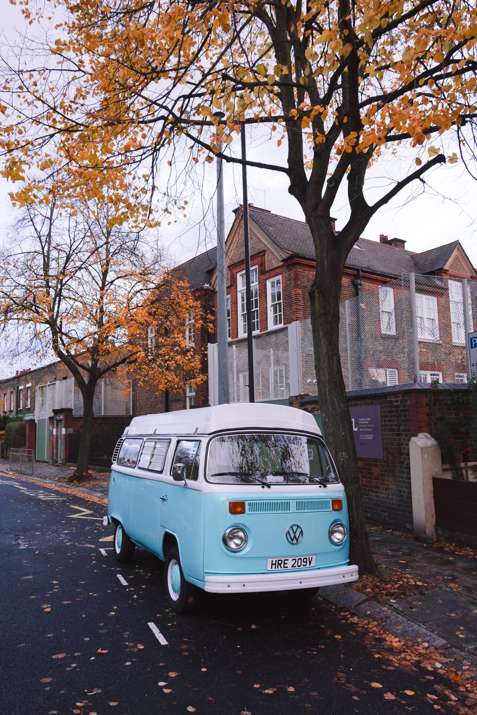teal Volkswagen Transporter parked beside curb