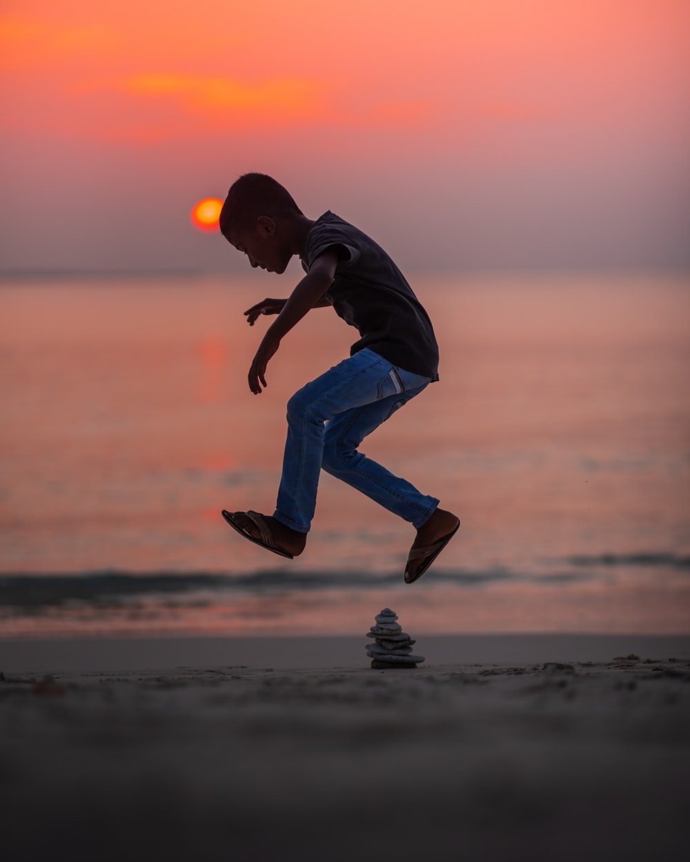 boy jumping near stack of stones on seashore during golden hour