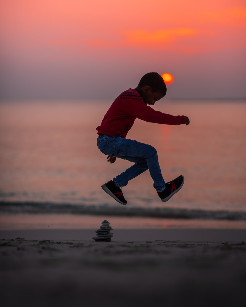 boy jumping on seashore during golden hour