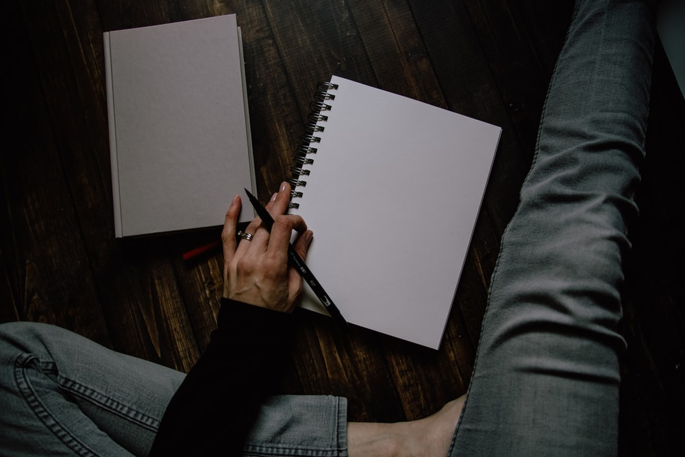 person holding black ballpoint pen and spring notebook