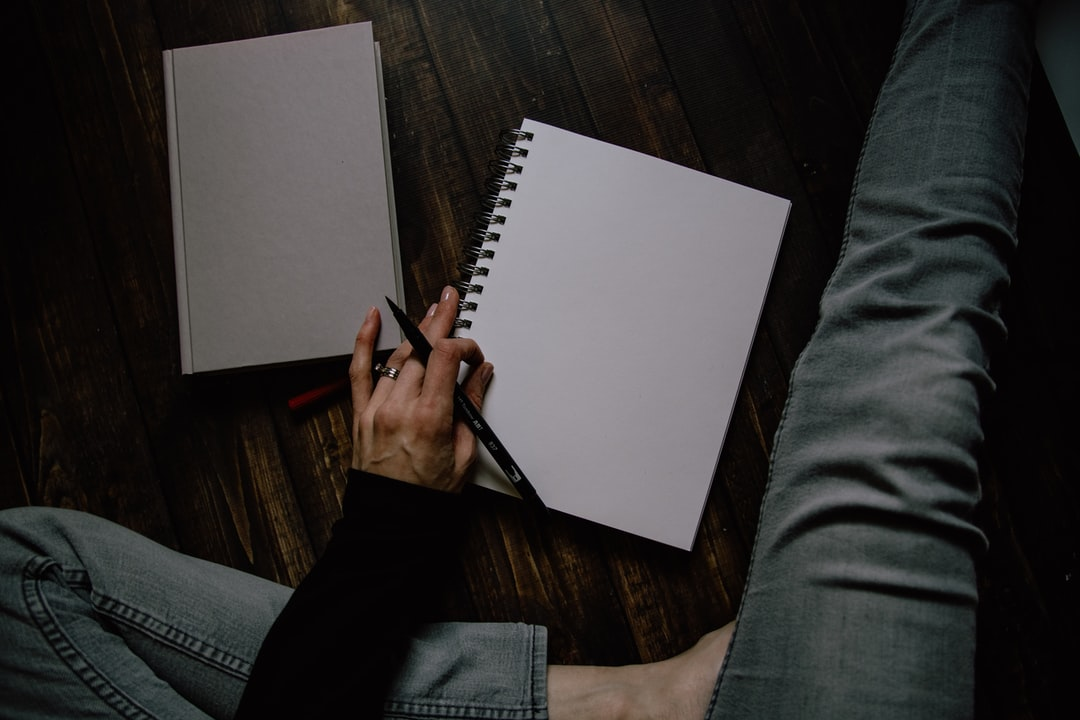 Woman Writing In A Blank Spiral Notebook - unsplash