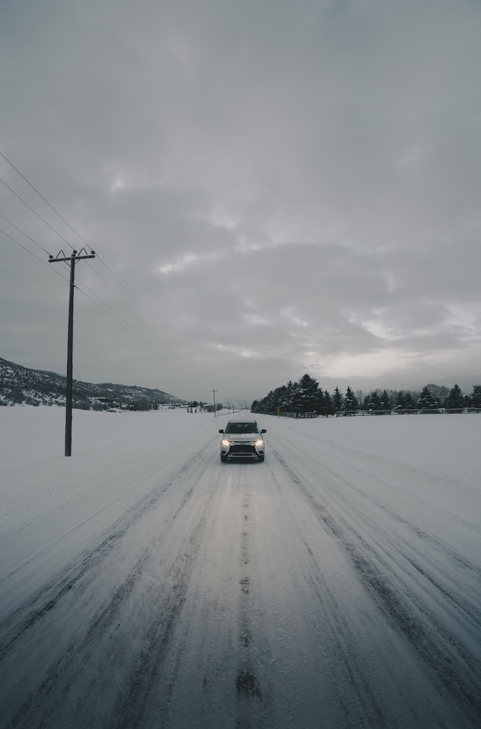 white vehicle on road covered with snow
