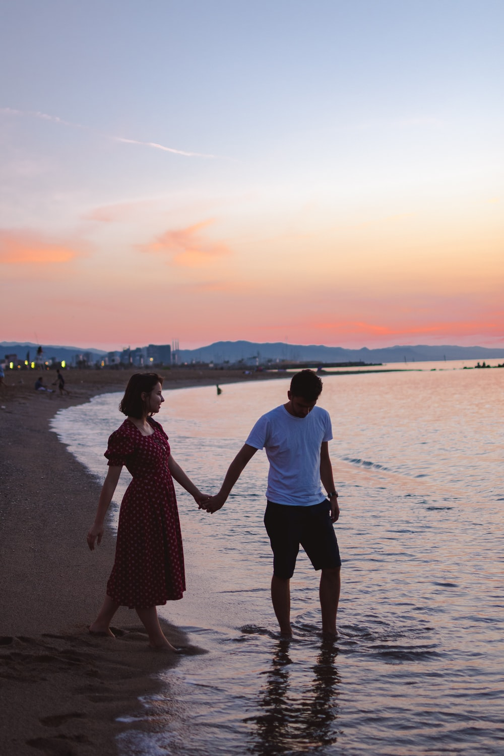 man and woman walking on seashore and holding hands during golden hour