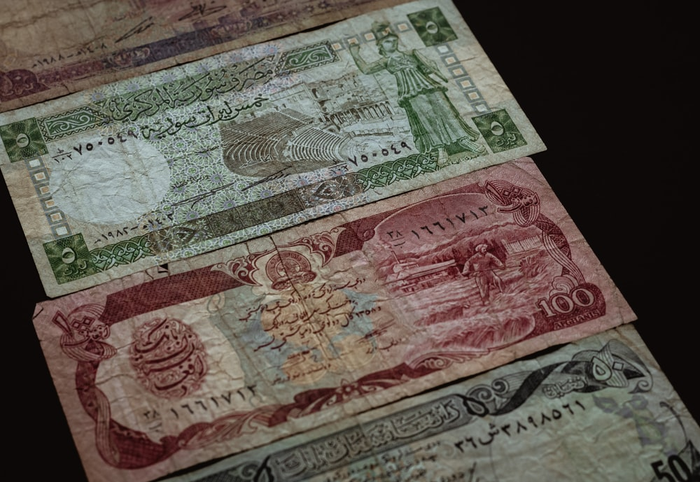 three banknotes on brown surface