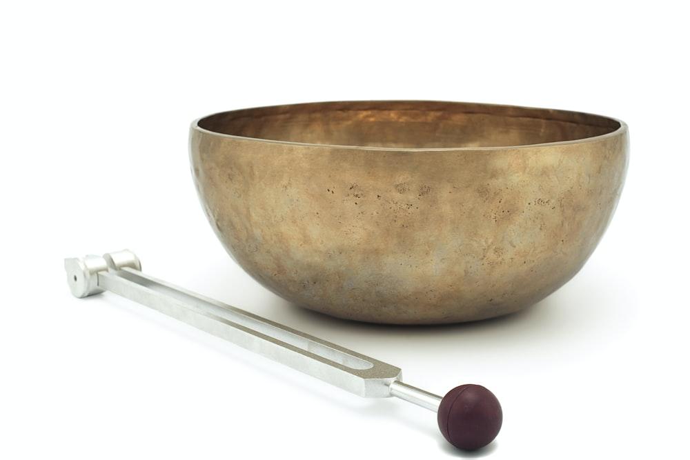 stainless steel spoon beside brown ceramic bowl
