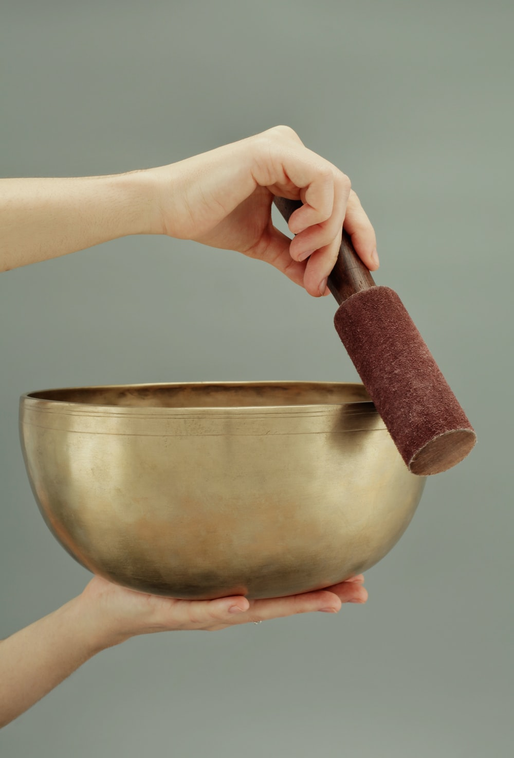 person holding brown clay pot