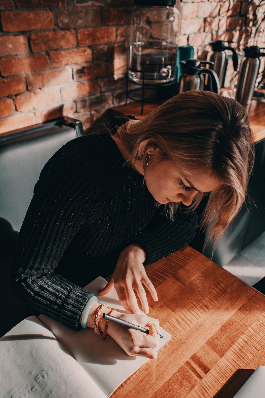woman in black sweater writing on book
