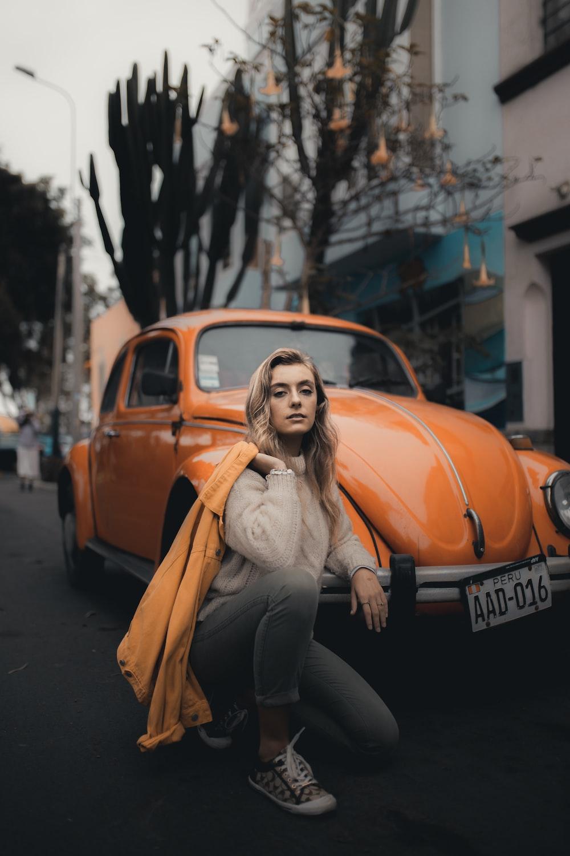 woman kneeling beside Volkswagen Beetle