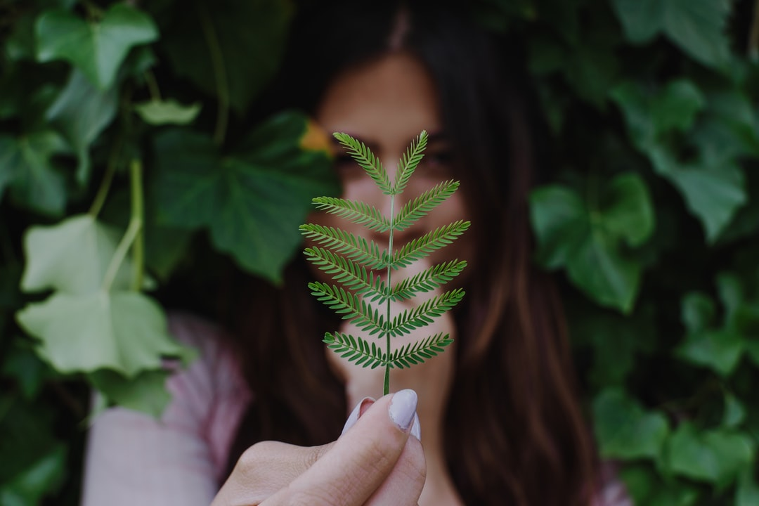 Latin Girl Holding A Leaf With Her Hands. - unsplash