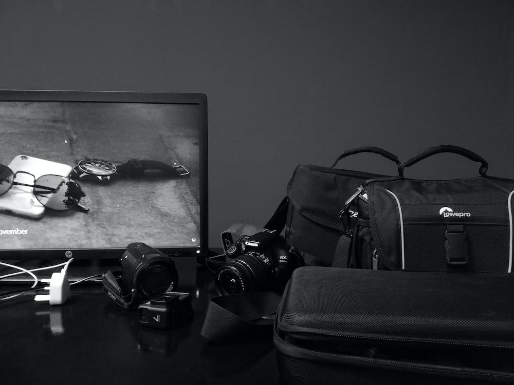 black dslr camera on black luggage bag