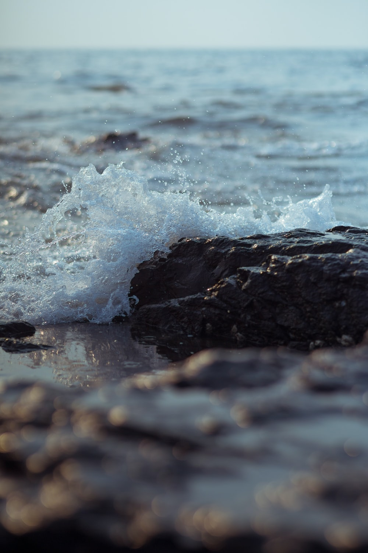 water waves hitting black rock