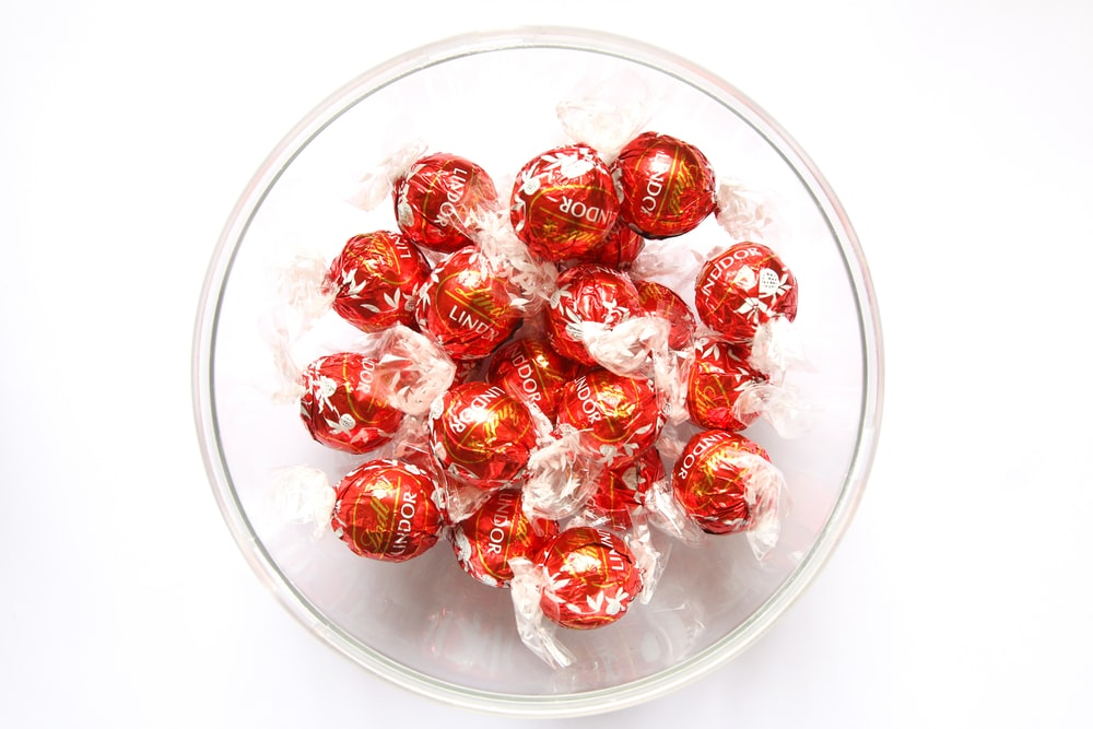 red and white round candies in clear glass bowl