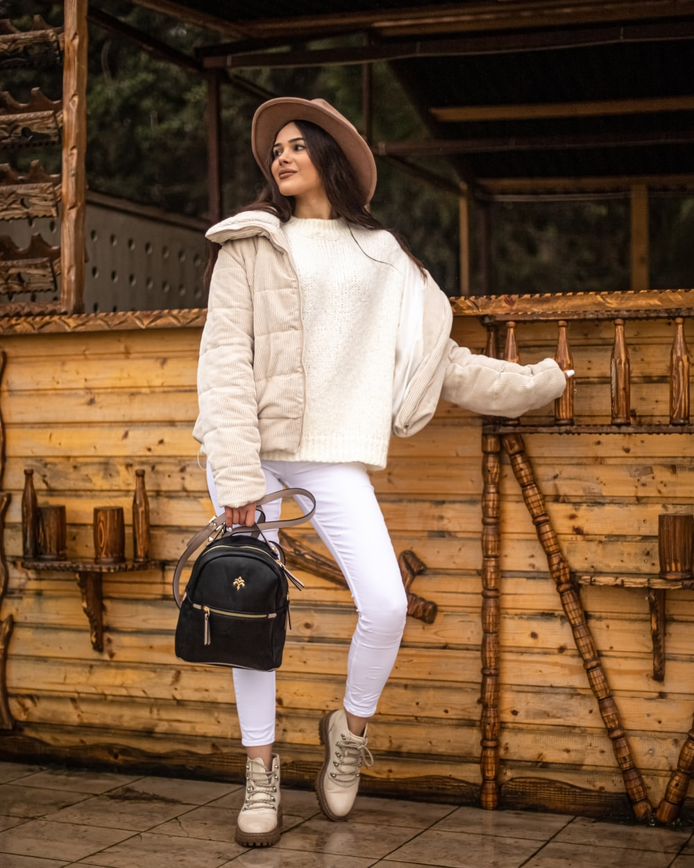 woman in white long sleeve shirt and brown pants holding black and gray backpack