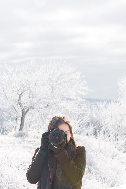 woman in brown jacket holding black dslr camera