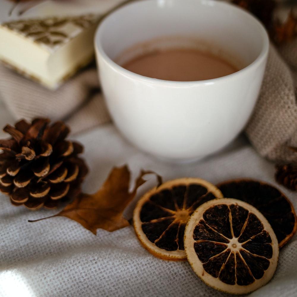 white ceramic mug with coffee beside brown leaves