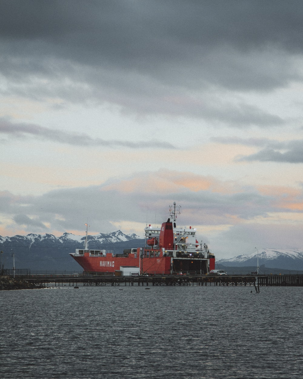 red ship on sea under cloudy sky during daytime