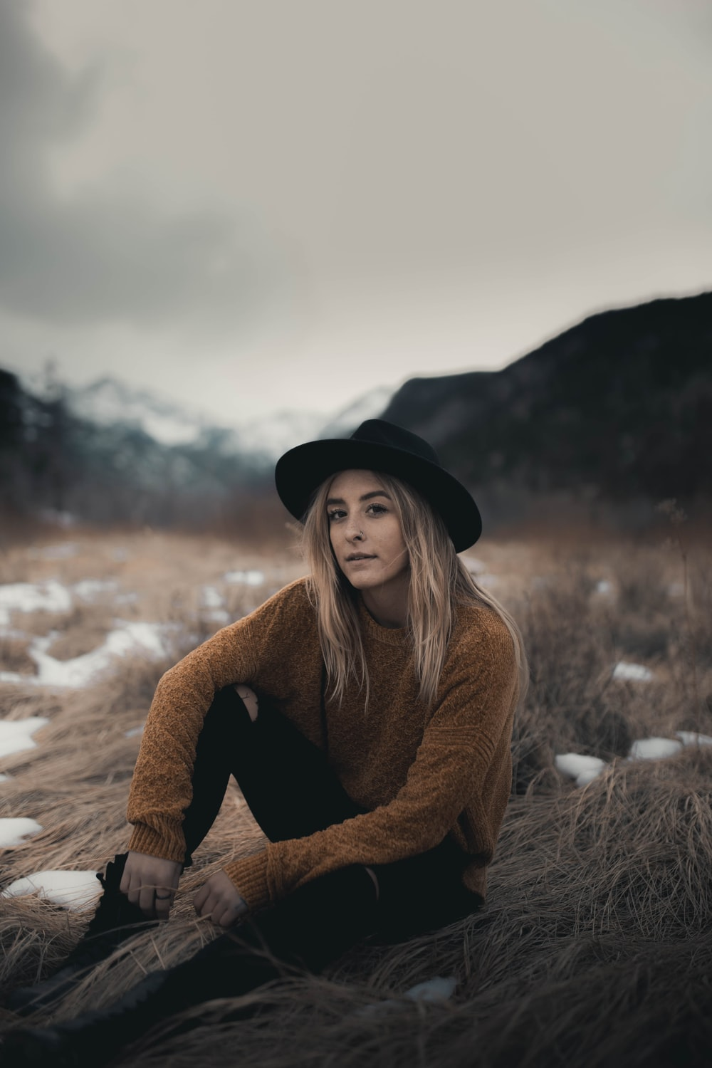 woman in brown sweater and black hat sitting on snow covered ground during daytime