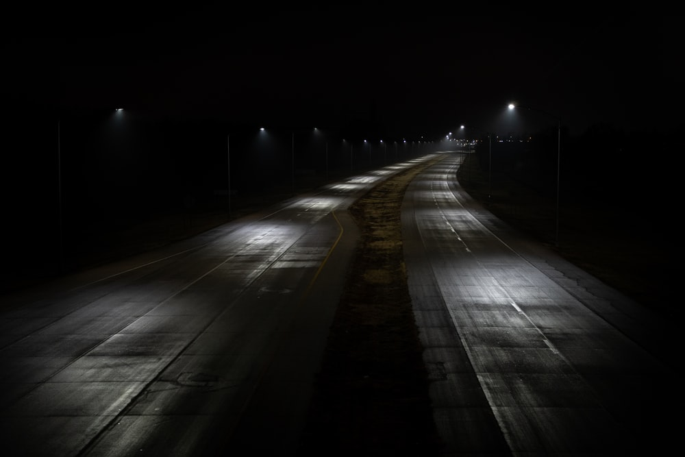 empty road with lights turned on during night time