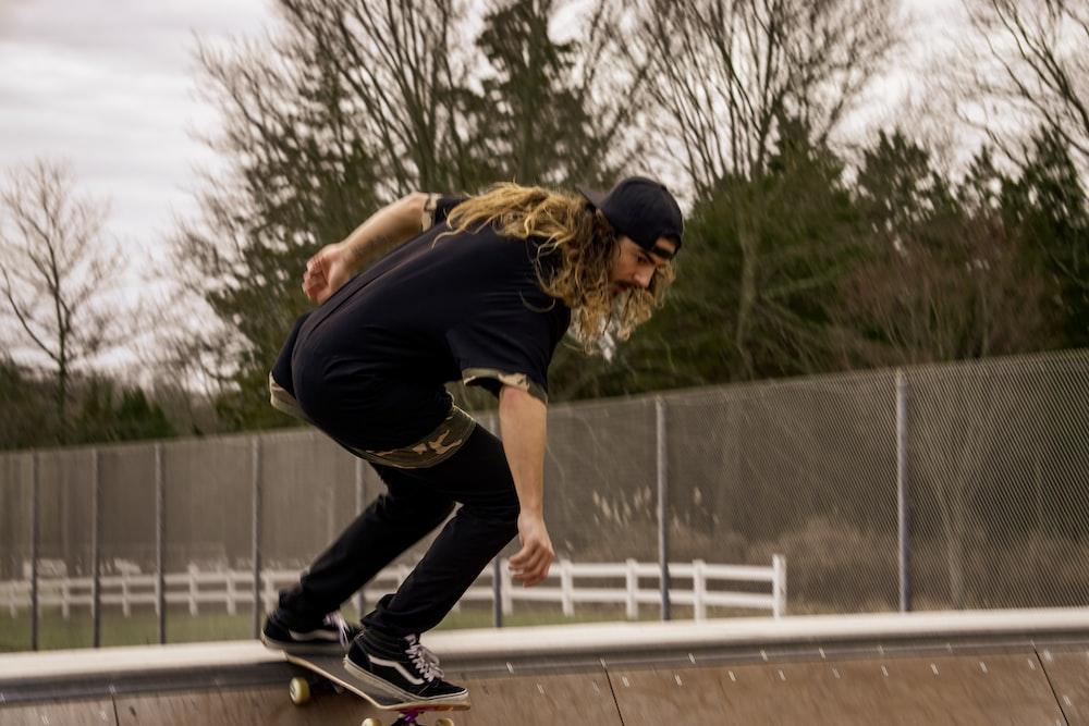 man in black t-shirt and black pants doing skateboard stunts during daytime