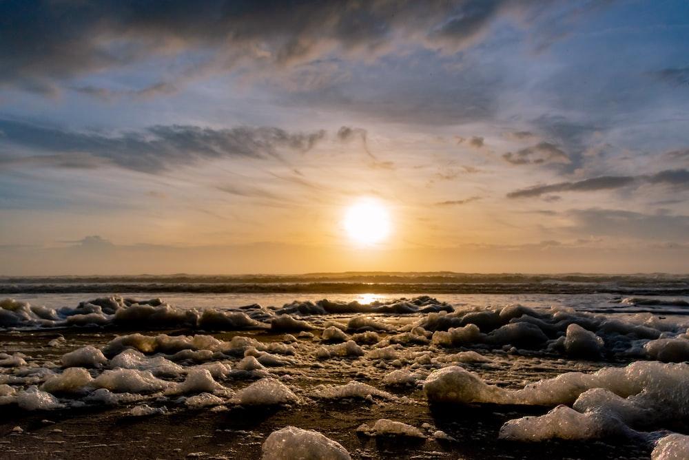 gray rocks on sea shore during sunset
