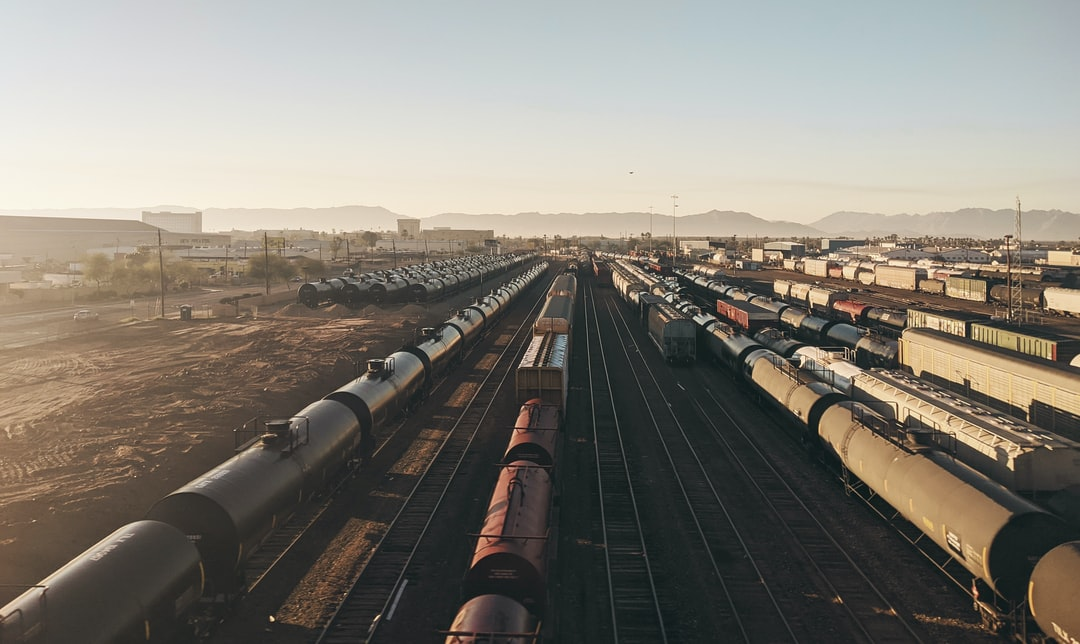 Looking at an aerial shot from a freeway onto a train yard during sunrise facing south.