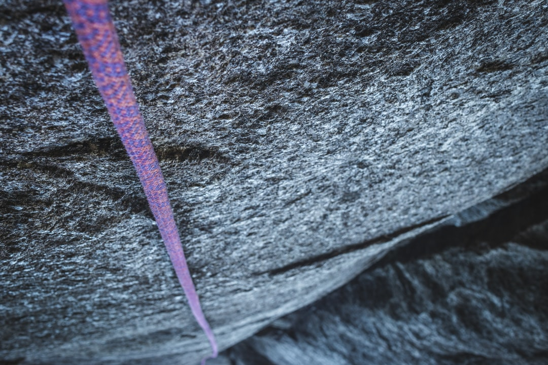 Climbing Rope Hanging Down Vertical Rock Face Very High - unsplash