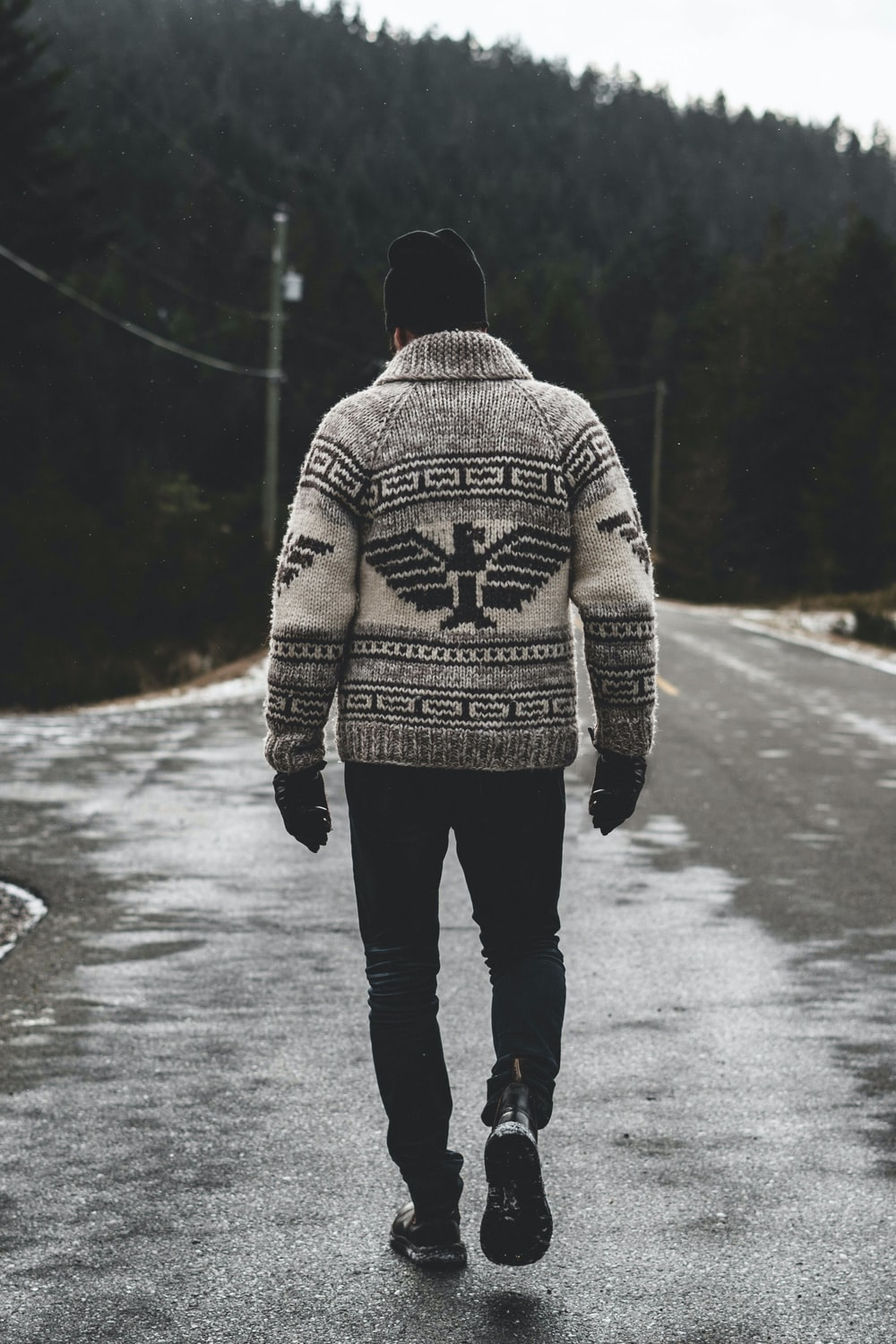 man in gray and black sweater standing on road during daytime