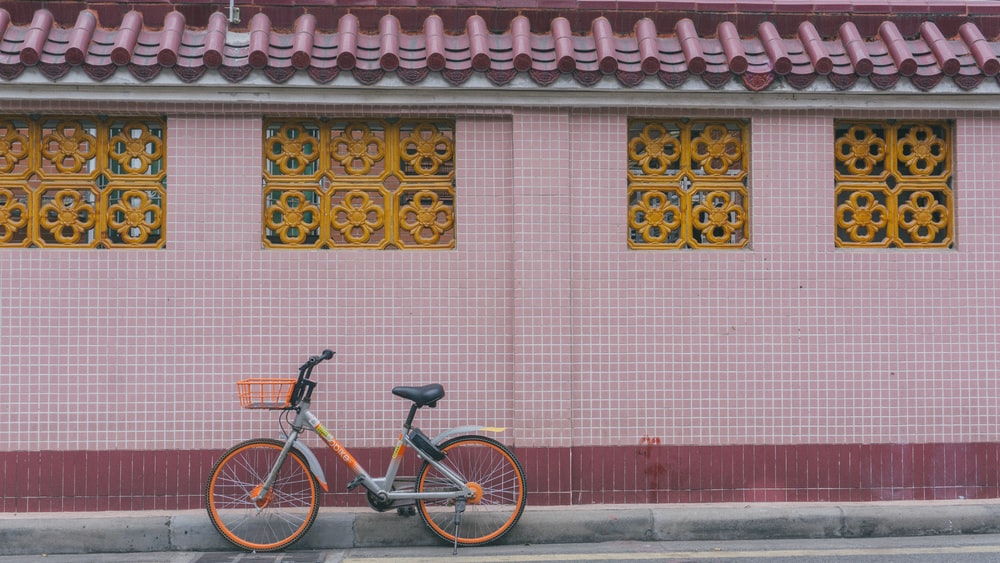 black bicycle parked beside red and white concrete wall
