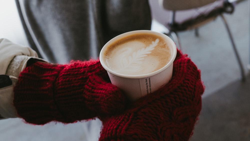 white ceramic mug on red knit textile