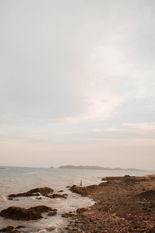 brown rocks on seashore under white clouds during daytime