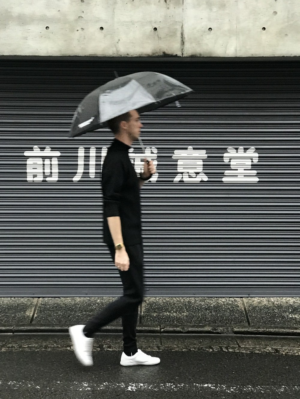 woman in black coat and black pants holding umbrella walking on sidewalk during daytime