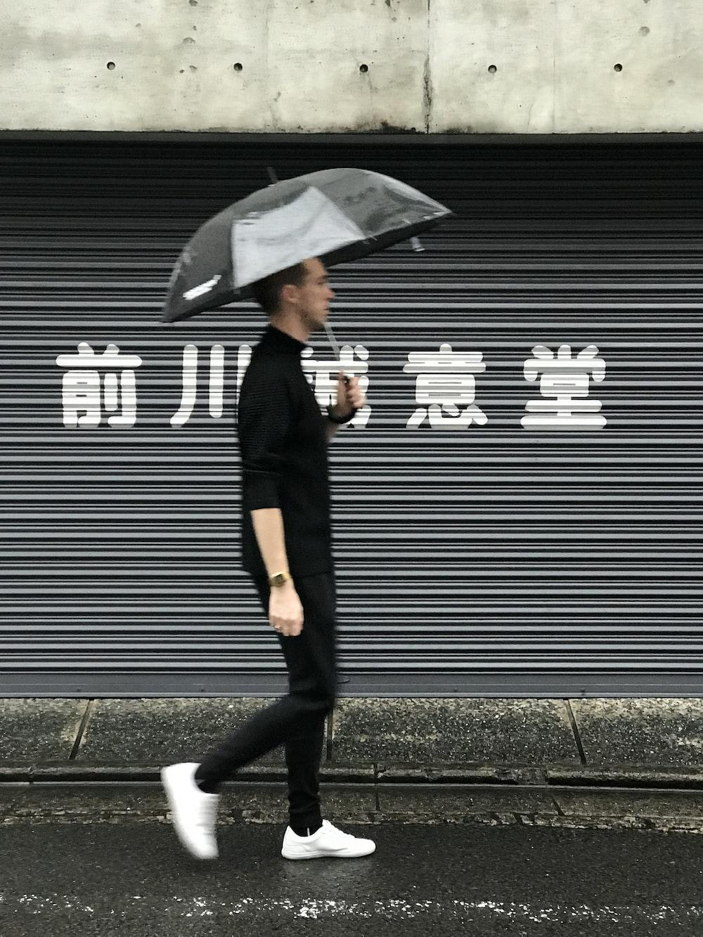 woman in black coat and black pants holding umbrella walking on sidewalk during daytime