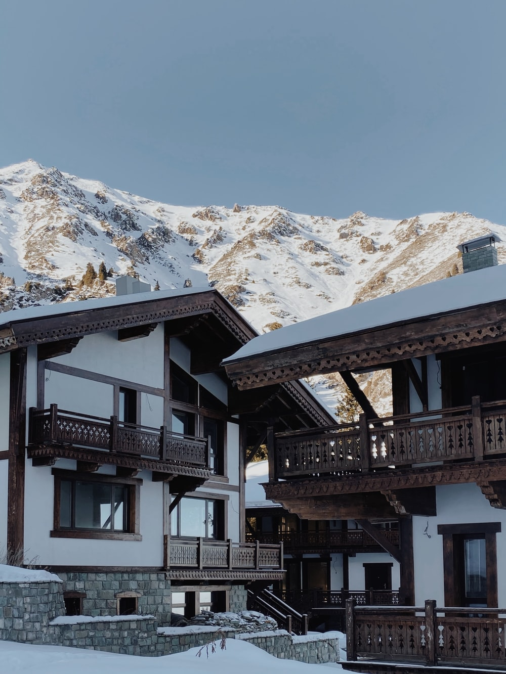 white and brown concrete house near snow covered mountain during daytime