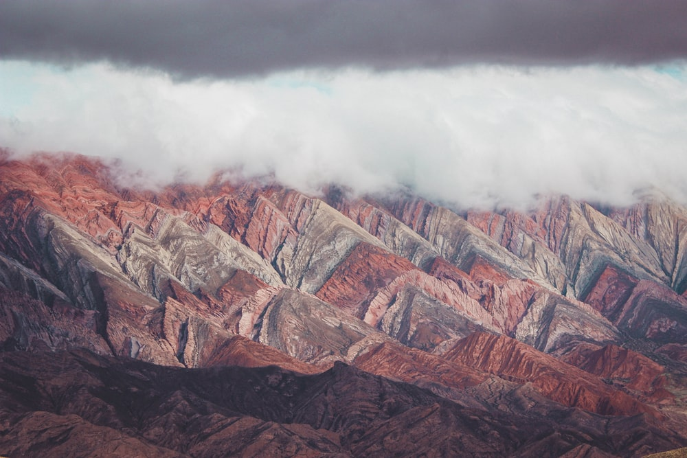 brown and gray mountain under white clouds