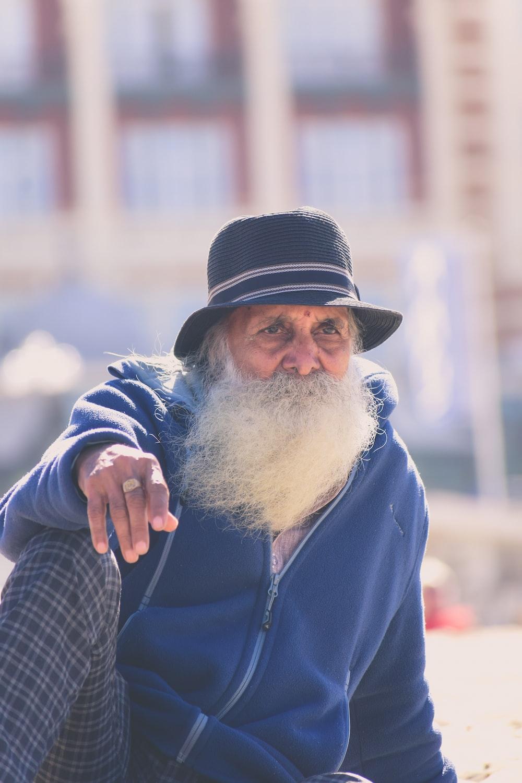 man in blue zip up jacket smoking