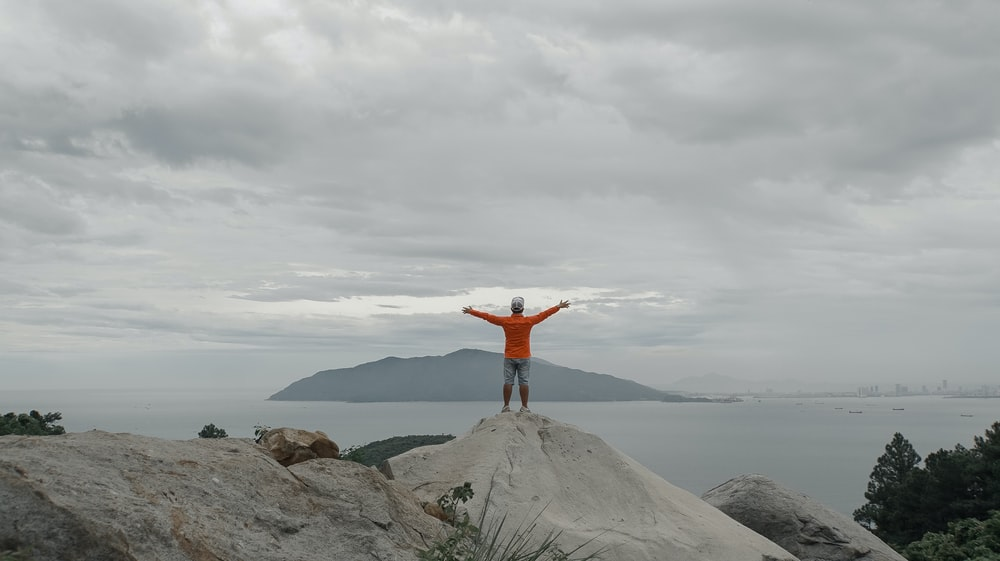 man in red jacket standing on gray rock formation under white clouds during daytime