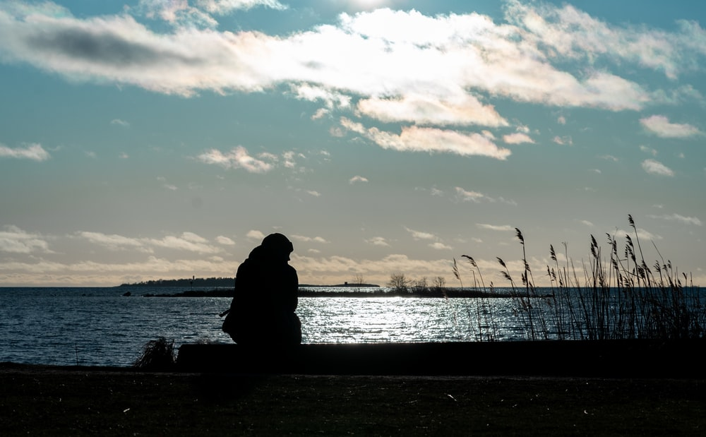 silhouette of person sitting on bench near body of water during sunset