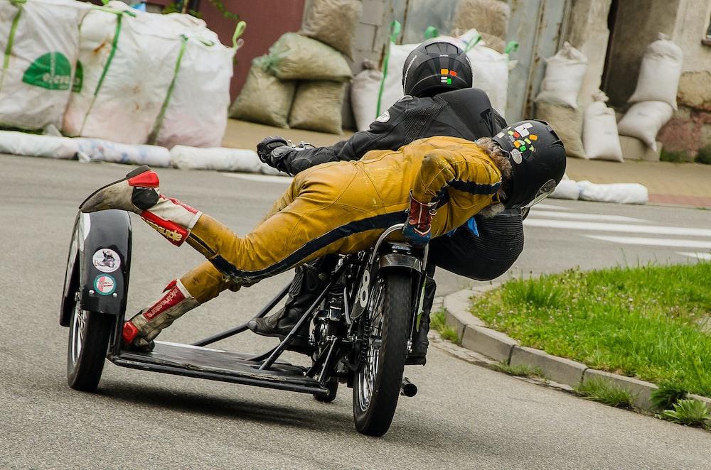 man in yellow jacket riding on black bicycle during daytime
