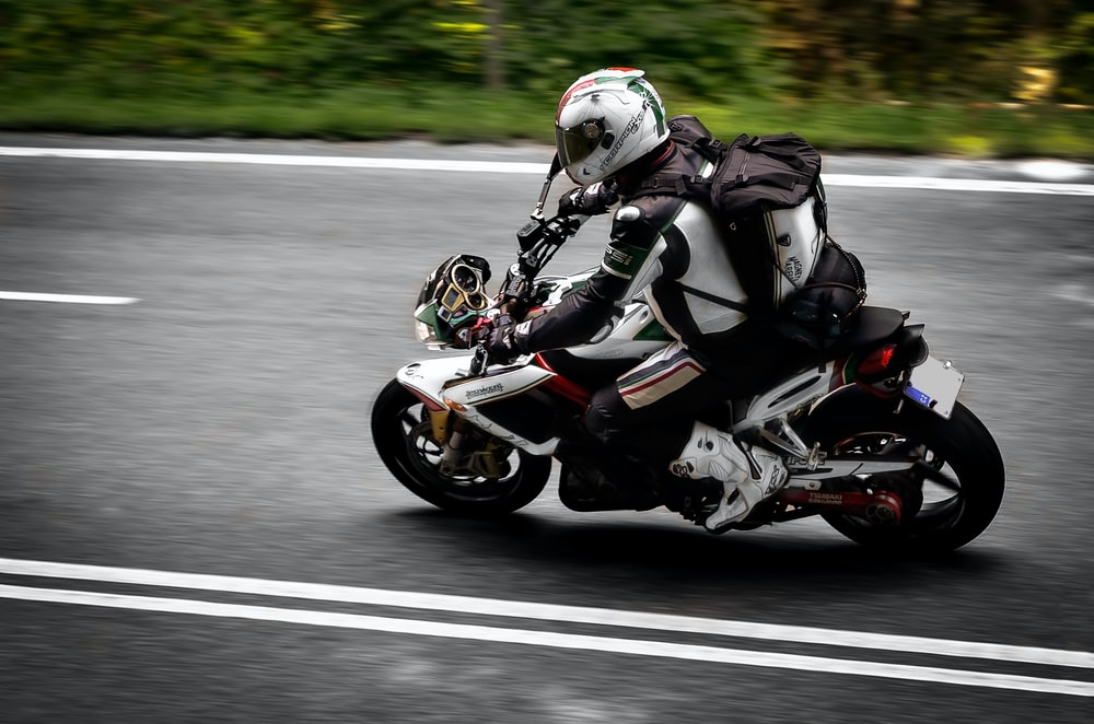 man in black and white motorcycle suit riding motorcycle on road during daytime